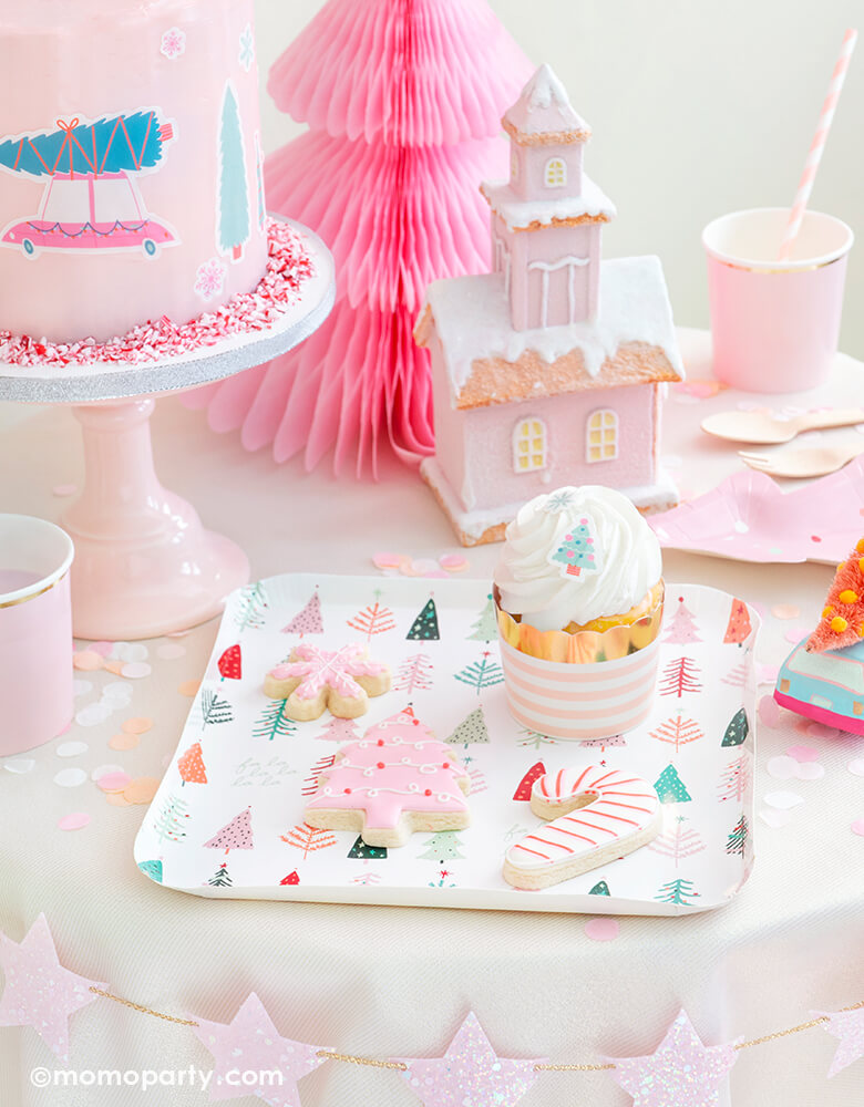 Momo Party Holiday Christmas Falala Holiday Table set up look with a pastel pink christmas tree, candy cane, pink snowflake cookies, cupcake with Blush Striped Food Cups on My minds eye's Falala Christmas Tree Plates, strawberry milk in the Pale Pink Tumbler Cup, Fa La La Christmas Tree Plates, pink buttercream cake with Let's Get A Tree! Cakescape Edible Stickers, Pink, Coral and Blush Candy Artisan Confetti on the table, StudioPep Pink Glitter Star Banner on the side of the table for a cozy celebration