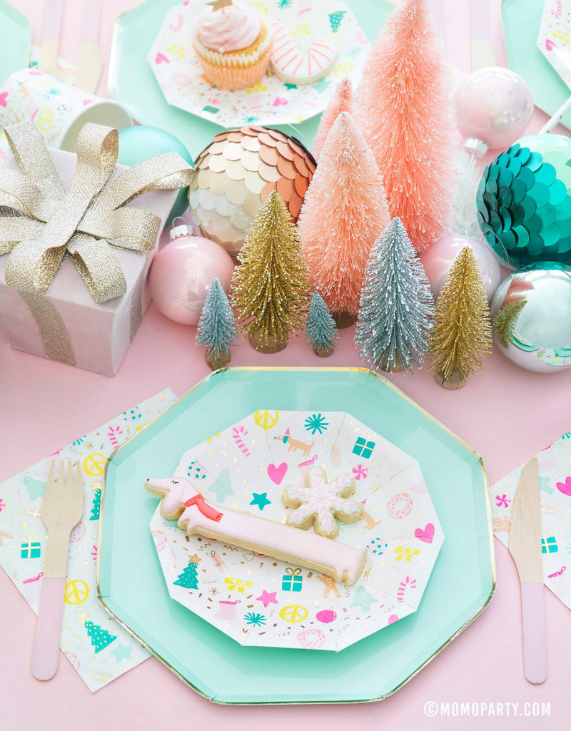 Merry and Bright Pastel Christmas table set up with cookies on top of Meri Meri Mint Large Dinner Plates and Daydream Society Merry and Bright Holiday Christmas Party Plates,Napkins and Cups, Pink wooden utensils, and gift box, Christmas Ornaments, mini pastel Sisal Trees as center piece for a pastel Christmas party celebration
