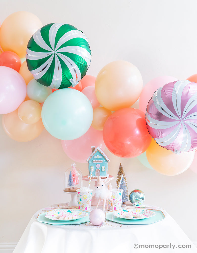 Merry & Bright Christmas Holiday Boxes with Pastel Color themed mint, peach, pink balloon garland and CANDY SWIRLS FOIL MYLAR BALLOON as backdrop, Meri Meri Mint Large Dinner Plates, and Day dream societyMerry and Bright Small Plates, Napkins and Cups as tablewares for a modern cute pastel holiday party idea