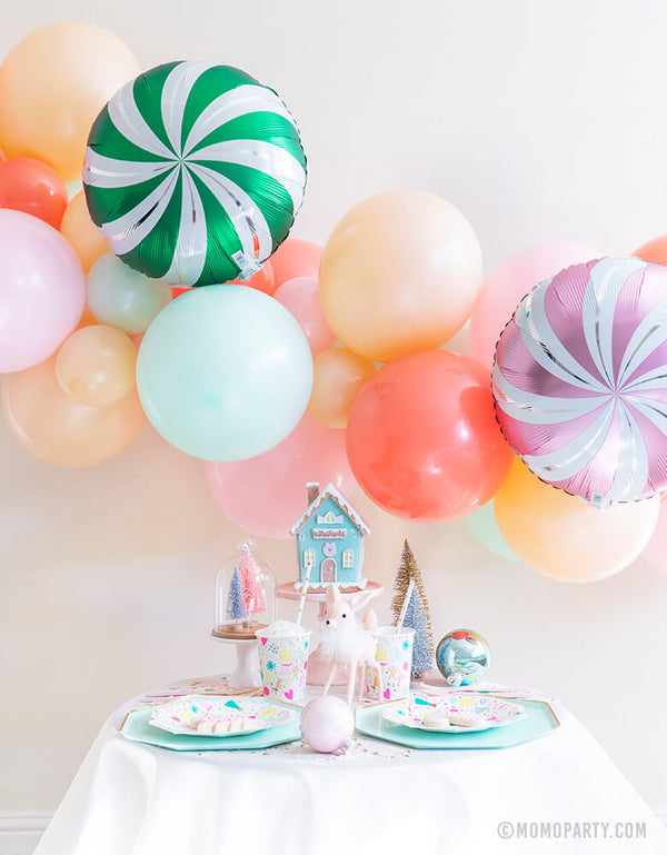 Merry & Bright Christmas Holiday Boxes with Pastel Color themed mint, peach, pink balloon garland and Satin candy swirls foil balloon as backdrop, Meri Meri Mint Large Dinner Plates, and Day dream societyMerry and Bright Small Plates, Napkins and Cups as tablewares for a modern cute pastel holiday party idea