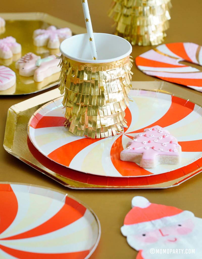 Holiday table setup with a gold star straw inside of Meri Meri Gold Fringe Party Cup, Gold Large Dinner Plates, with Peppermint Swirl Side Plates layered on top, and pink christmas tree cookies. a Santa Napkin and peppermint napkin on the side. with a pink christmas themed cookies in a gold side plate,  for a Gold Red Peppermint Glam Christmas party Celebration