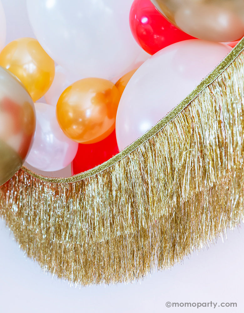Momo Party Holiday party decoration idea Featuring Gold, Red, Pearl White, Coral, Pearl peach latex balloons with Meri Meri gold tinsel fringe garland