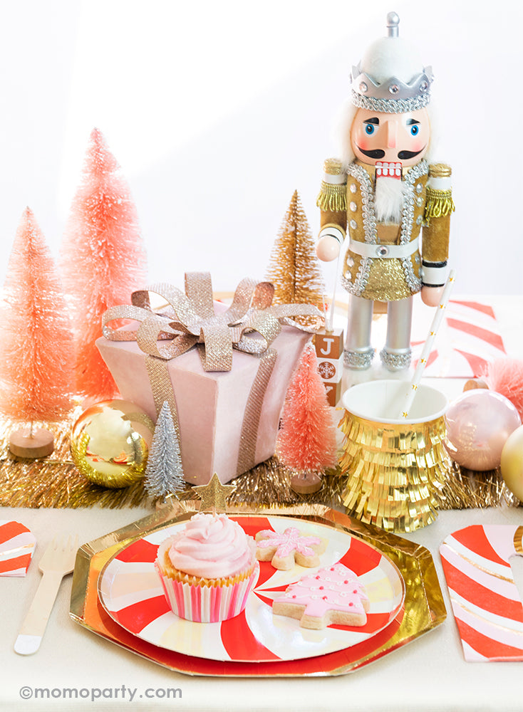 Momo party Holiday tablescape look with cupcake and pink christmas tree cookie, pink snowflake cookie on the  Peppermint Swirl Side Plates layered on top of Gold Large Dinner Plates, gold fringe cups and peppermint napkin on the side. with a pink christmas gift box, pink and gold Sisal Trees and a Nutcracker as centerpiece, ready for a modern classic look of Gold Red Peppermint Glam Christmas party Celebration