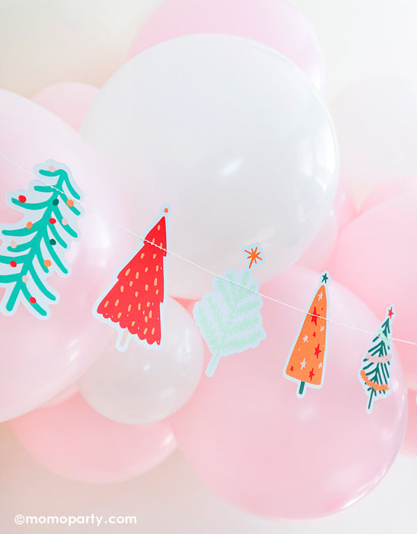 My mind's eye 6 ft long Holiday Fa-La-La Christmas Tree Banner, featuring many cute graphic die-cut tree. pair with pastel pink and white colored latex balloon garland for a fresh cute pastel pink holiday party, kids christmas party and all christmas related celebrations