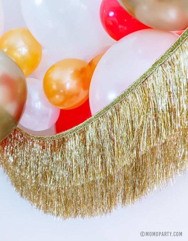 Momo Party Holiday party decoration idea feathered Gold, Red, Pearl White, Coral, Pearl peach latex balloons with Meri Meri gold tinsel fringe garland