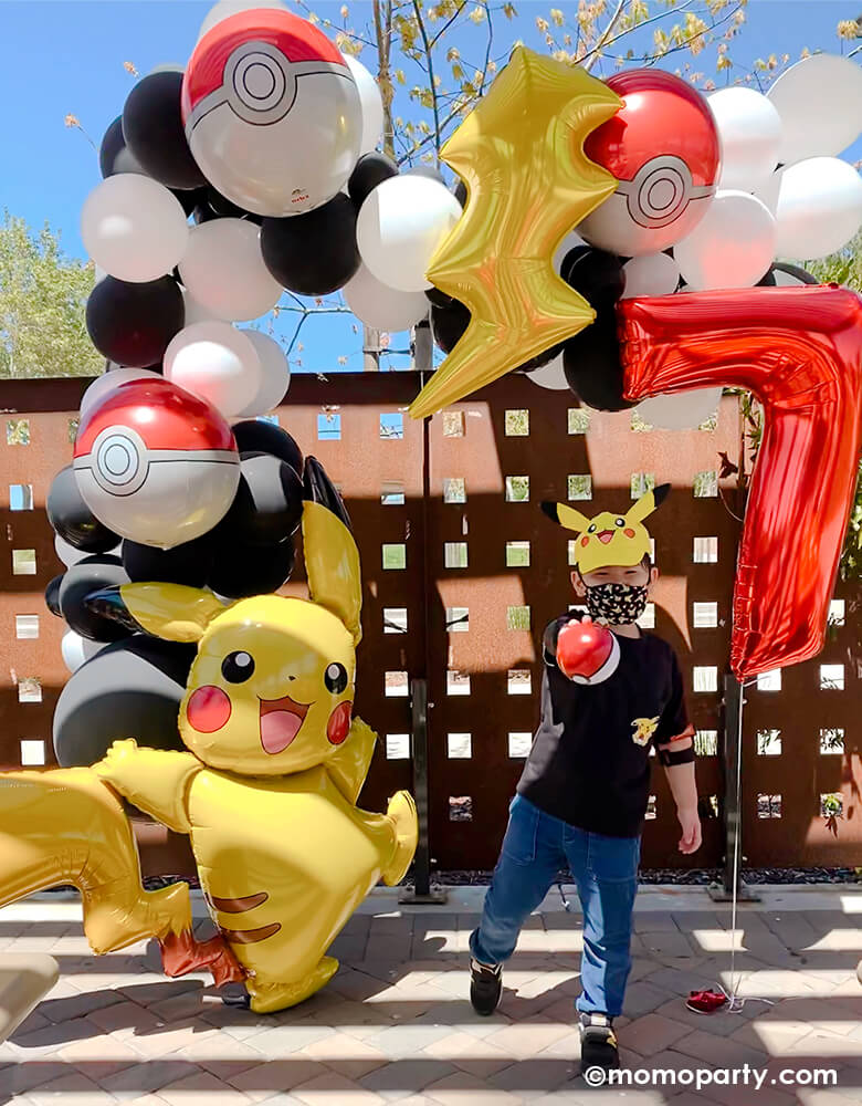 "A boy wearing pikachu hat, holding a pokemon ball on his hand, standing on his Pokemon themed birthday Party. Decorated with a Black and white latex balloon garland, mix with Pokemon Pokeball Orbz Foil Balloon and Lightning Bolt Foil Balloon. A anagram 57"" Pokemon Pikachu Airwalker Foil Balloon stand on the left, and a Large Number 7 Red Foil Mylar Balloon on the right side. A modern cute backdrop for a pokemon themed birthday party"