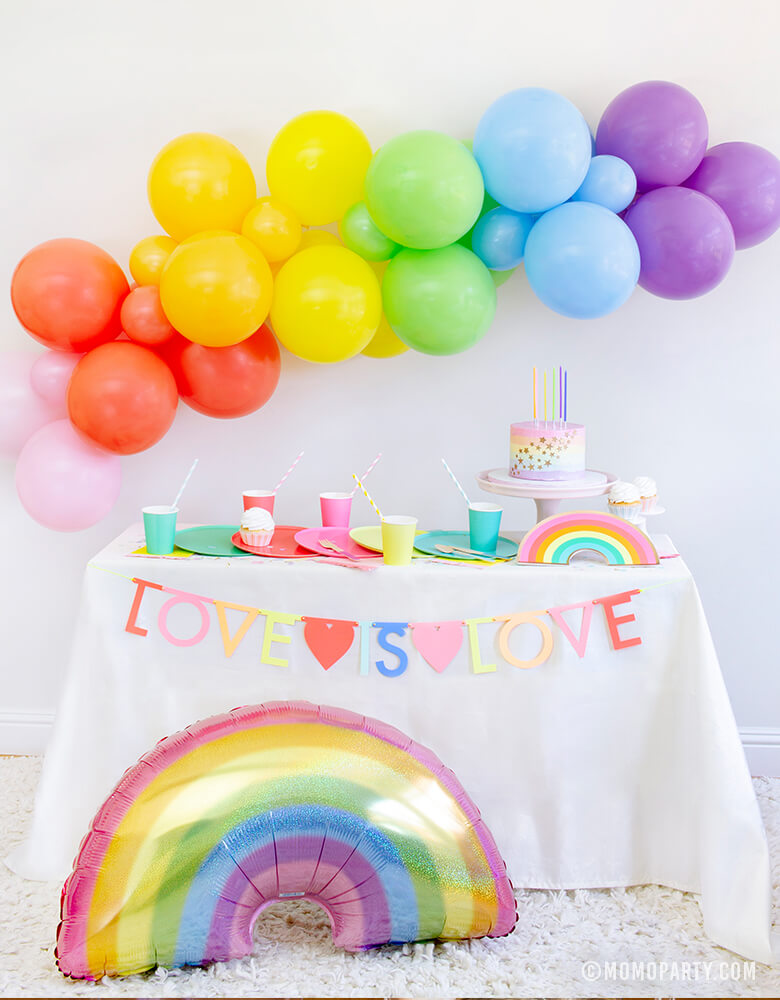 "Rainbow theme Pride Party, with Meri Meri Multicolor Letter Garland Kit with message of ""love is love"" and  HOLOGRAPHIC PASTEL GLITTER RAINBOW FOIL MYLAR BALLOON in front of rainbow themed dessert party table and"