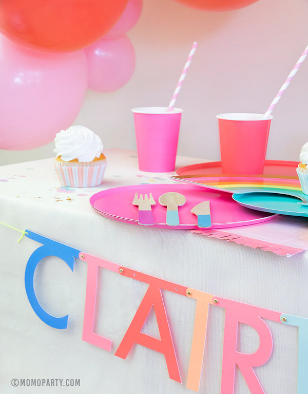 "Rainbow party table look with Oh happy day rainbow plates, cups, Meri Meri Multicolor-Make-Your-Own-Letter-Garland-Kit spelling of ""Claire is 6"" for a girl's rainbow birthday party"