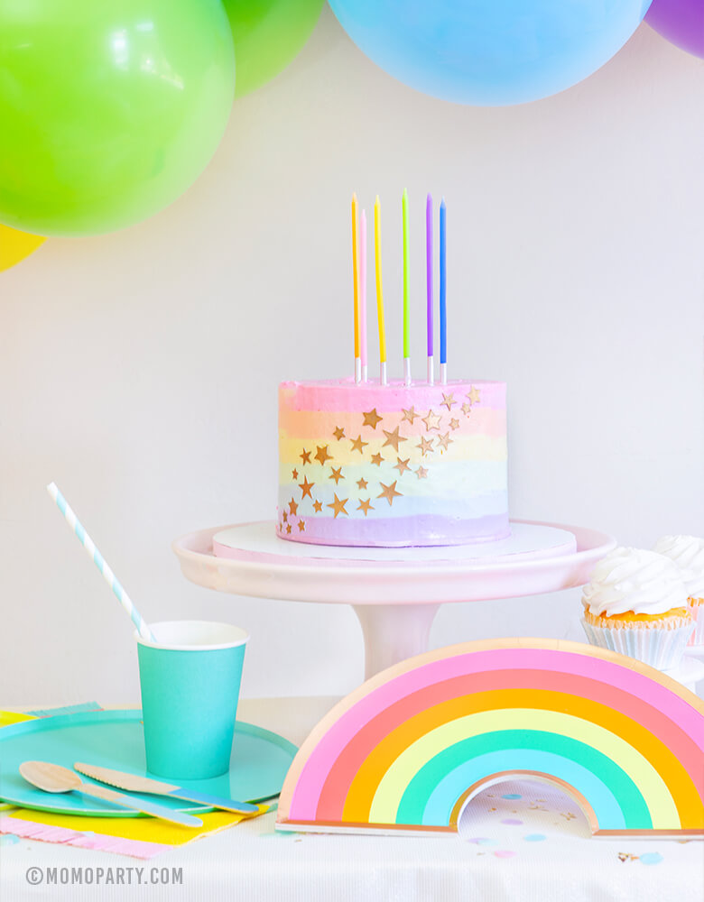 Modern Rainbow party look, Pastel Rainbow Birthday Slim Candles on a pastel rainbow buttercream cake with starts, Oh happy Day rainbow plate, cups, and colorful balloon garland