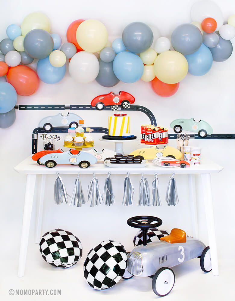 Momo Party Race Car Box, set up inspiration with Meri Meri race car paper plates, race car shaped napkins, race car party paper cups, black strip small plate, neon confetti flag cupcake kit, CandyLab race car wooden toys on top of cake, Fuel treat favor box with popcorns, all on dessert table.  colorful balloon cloud, Road tape with Car plates and Backdrop decorations. Checkerboard foil balloon and Race Car Rider toy for a modern Race car, car themed birthday party