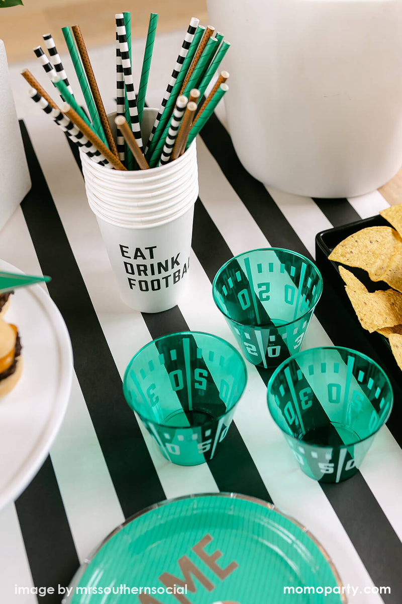 Football Party inspo, close up table look with cakewalk true brands Green Game on Football Party Paper Plates, Yard Line Plastic Cups, Football Tailgate Party Straws inside of Eat Drink Football Paper Cups, chips on the black container on the side, with on top of the Hester & Cook simple striped runner. These modern table styling are perfect for super bowl party and entertaining with family and kids