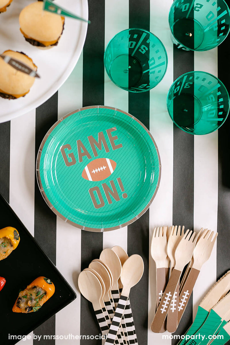 American football Party inspo, top view of cakewalk true brands Green Game on Football Party Paper Plates, Yard Line Plastic Cups, Football Tailgate Wooden Cutlery Set, some small bites on top of Hester & Cook simple black and white striped table runner. These modern designed party ware are perfect for a super bowl party and football themed birthday, or any entertaining with family, friends and kids