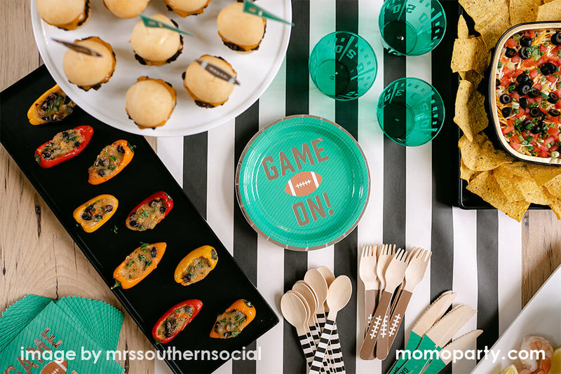 Flat top view of American Football Party table. Layout with cakewalk true brands Green Game on Football Party Paper Plates, Yard Line Plastic Cups,Football Tailgate Wooden Cutlery Set, some small bites, chips around, with Hester & Cook simple black and white striped table runner. These modern partyware are perfect for super bowl party, football themed birthday, any seasonal sport game party, football fan's game day, or any entertaining with family and kids
