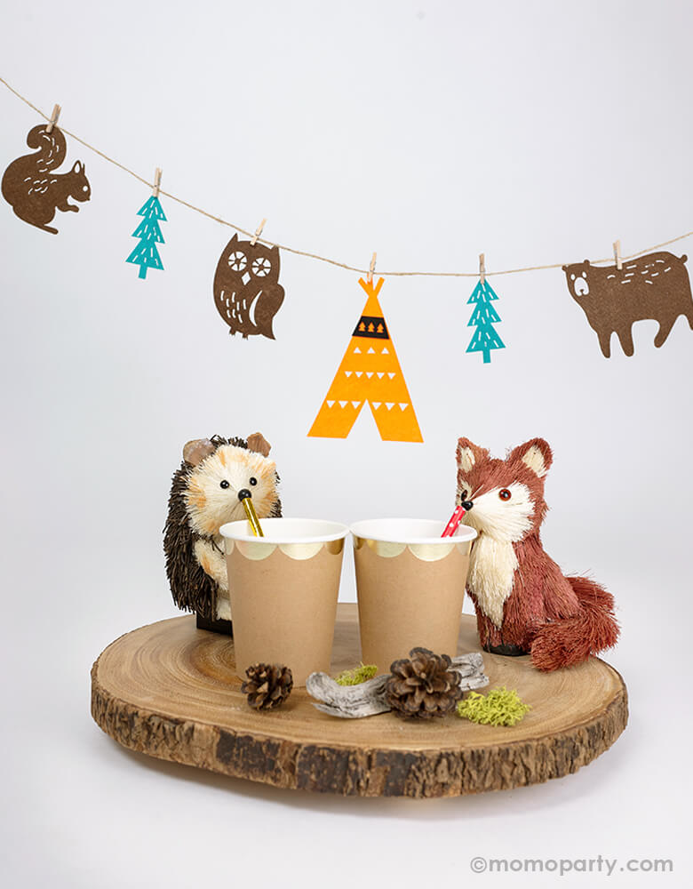 Mini woodland party decorated with a cute Hedgehog and fox figures drinking from a gold scoplated paper cups, with pinecone around them and  a woodland felt garland hanging behind them. this woodland felt garland features one teepee, five animals, and three trees. With mini wood clothespins, this set is easy to put together and creates a lovely charm to your woodland celebration