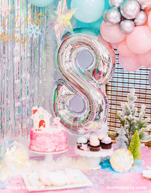 a Dreamy Winter Wonderland themed 8th years birthday Party set up with large number 8 silver foil balloon, in front of iridescent curtain, with iridescent hanging starts, desserts and cake on top of pink table cloth with christmas tree decorations