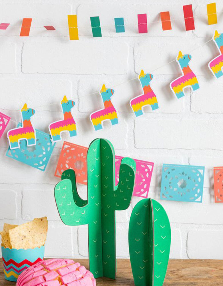 My-Minds-Eye-Fiesta-Mini-Banner-Set with ticker tape banner, llama banner, and papel picados banner hung on the wall with cactus decoration as centerpiece on the table