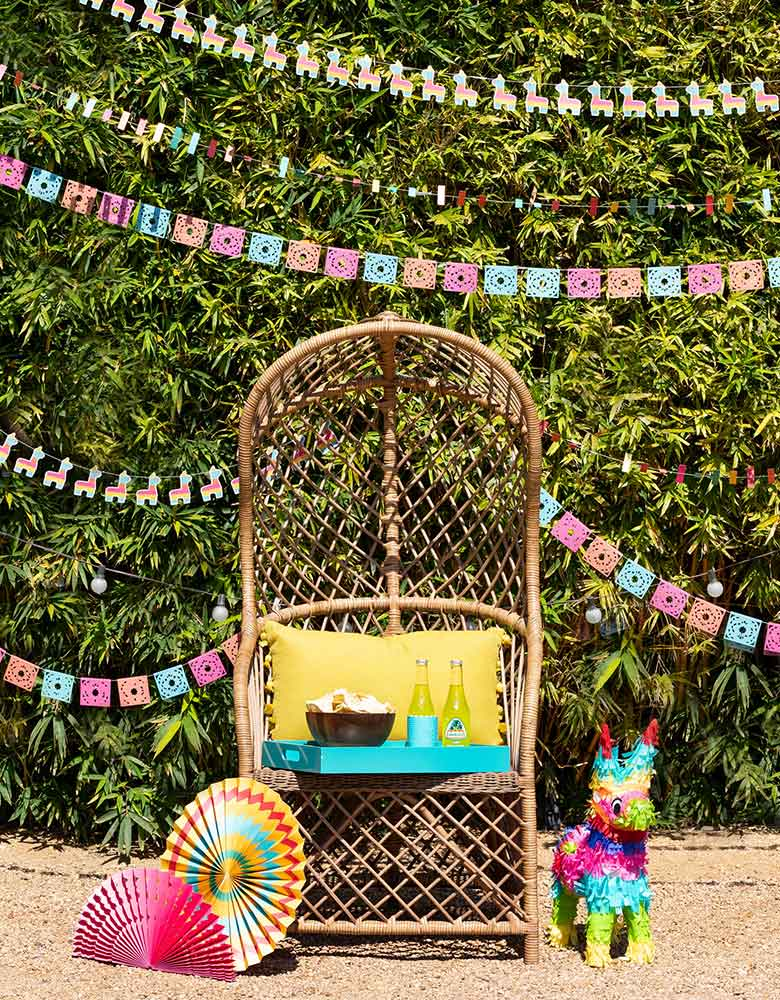 My-Minds-Eye-Fiesta-Mini-Banner-Set with ticker tape banner, llama banner, papel picados banner and mini cactus banner hung on top in a fiesta themed party with colorful decorations including party fans and piñata