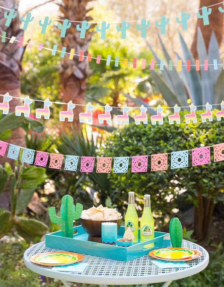 My-Minds-Eye-Fiesta-Mini-Banner-Set with ticker tape banner, llama banner, papel picados banner and mini cactus banner  hung  on top of a party table with cactus decorations for a fiesta themed party