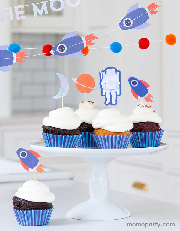 Space themed birthday party, a white cake stand on kitchen countertop filled with cupcakes decorated with My Mind's Eye - Rocket Cupcake Kit. with the look of rockets, stars, planets and astronauts topper and blue stripe wrappers, a rocket banner hanging around.