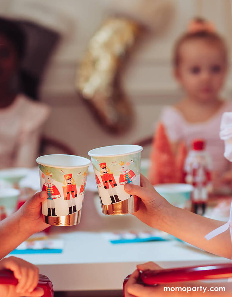on a warm cozy Holiday dinner table, the little hands cheers with holding Nutcracker Holiday Party cups, there cookies on the cake stand. little friends sitting around, these paper cups printed with whimsical classic Nutcracker characters of Nutcracker, Mouse King designs, these high quality eco friendly party cups look so on theme for your home or a nutcracker lover christmas party