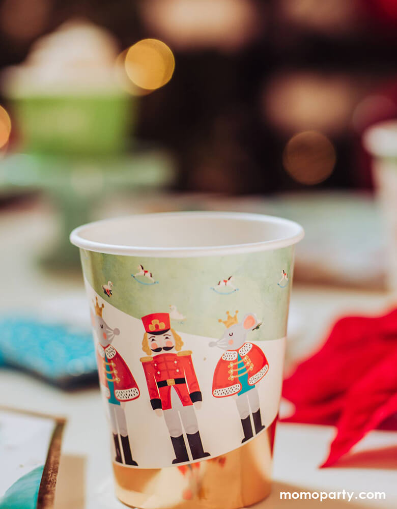 Cozy Holiday party table close up details of a Nutcracker Holiday Party cups, printed with whimsical classic Nutcracker characters of Nutcracker, Mouse King designs. for a warm cozy holiday dinner. these high quality eco friendly party cups  will set a scene worthy of a standing ovation for your home or a nutcracker lover christmas party