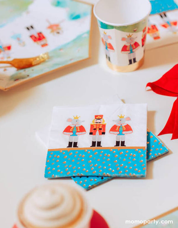 Holiday party table close up of Crated party Nutcracker Holiday Party Napkins, with whimsical classic Nutcracker characters, like Nutcracker, Mouse King designs, and nutcracker holiday party cups and plates, red ribbon, gold folks around. Adding these well designed party supplies to set a scene worthy of a standing ovation for your home or a nutcracker lover christmas party
