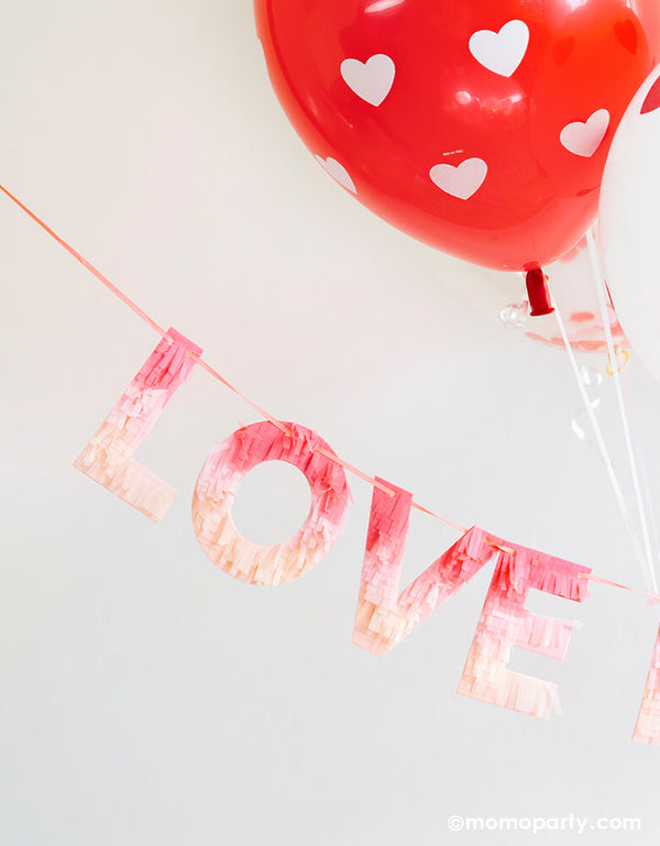 "Valentine day Room decoration with Meri Meri Ombre Love Garland made with fringed tissue paper, letter ""love"" in red, peach and pink ombre effect colors, with big heart printed Red latex balloon"