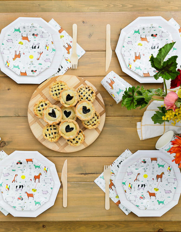 Kids Farm Barnyard Party table set up with On-The-Farm-Animals Small Plates, Napkins, wooden utensils, flowers and blueberry cookie, pies