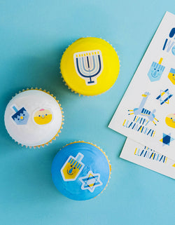 blue, yellow and white cupcakes decorated with Make Bake shop Oy To The World Edible Decorating Stickers, include edible stickers with many cute Hanukkah symbols illustration like Jews light candles, Menorah, dreidels, Gold Coins. Simply peel it and apply to iced cakes, cupcakes, cookies, These easy baking hacks will be make decorating baked goods so much easier to this Hanukkah