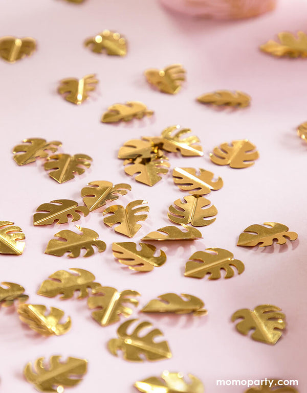 Party Deco Palm Leaf Gold Confetti on the pink table cloth. This confetti features Palm leaf shape cutouts with gold foil. Add some fun to your jungle, dinosaur or tropical themed party by spreading this set of palm leaf confetti in metallic gold to your table! party supply accessories Sold by Momo party store provided modern party supplies, boutique party supplies, chic holiday party supplies and high end party supplies