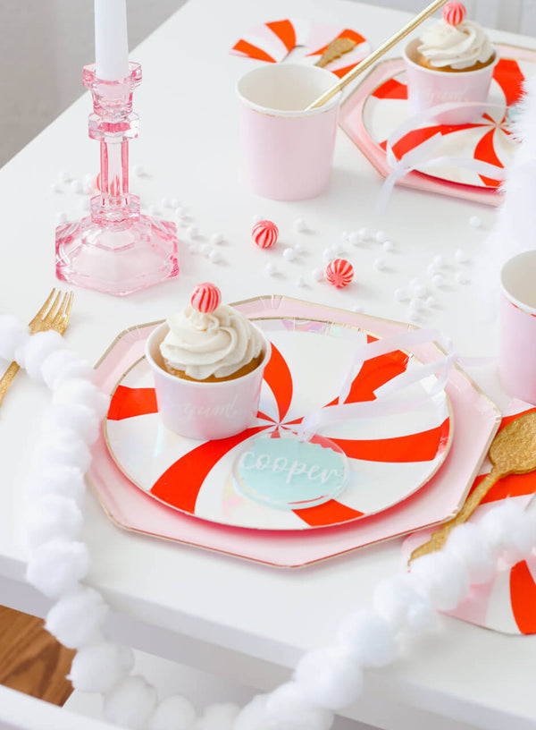 A Christmas Party Tablescape idea with Peppermint Plate Layerd with Dusty Pink Plates, along with candy cane napkins and pale pink tumbler cups