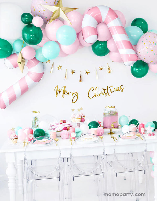 Pink Christmas Party Ideas by Momo Party featuring Party Deco's Pink Candy Cane Foil Balloon on a festive balloon garland in pink, mint and green colors above a festive party table filled with Christmas themed party goods