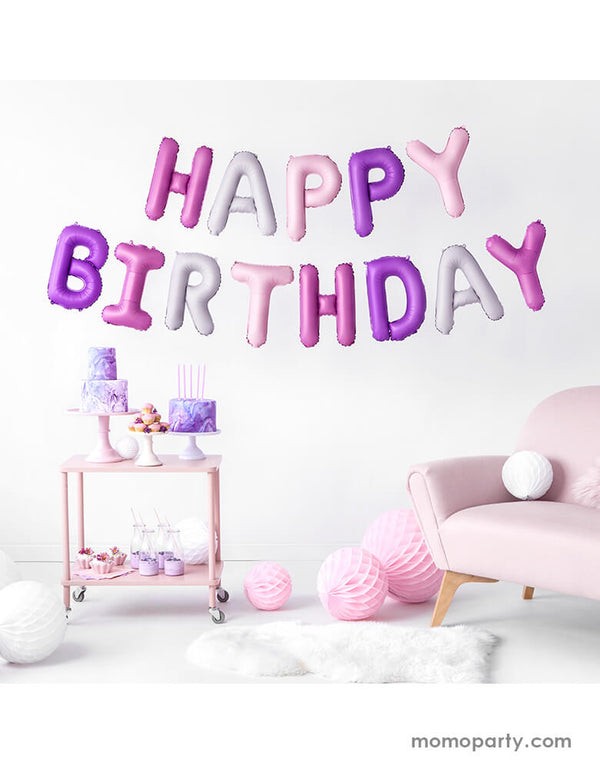 An at-home birthday party with pink couch and pink purple cakes and sweets with Party Deco's Pink Happy Birthday Foil Balloon Set in difference shade of pink hung on the wall for a girl's birthday