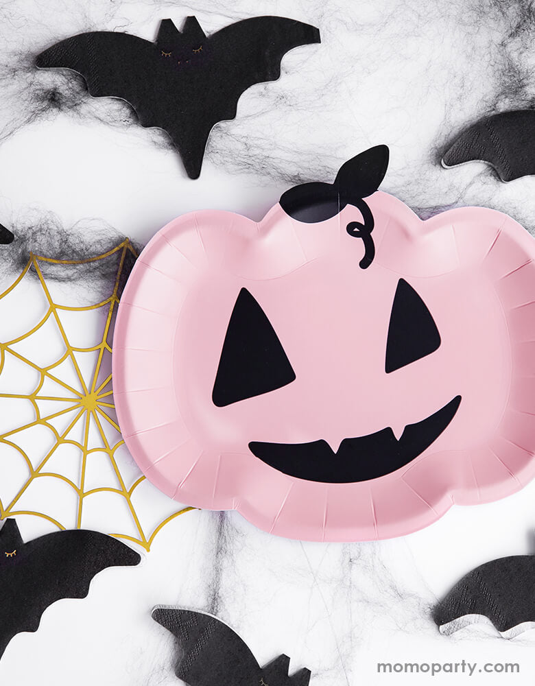 A spooky Halloween table featuring Party Deco Pink Pumpkin Plates surrounded by Bat napkins and gold spider web decorations