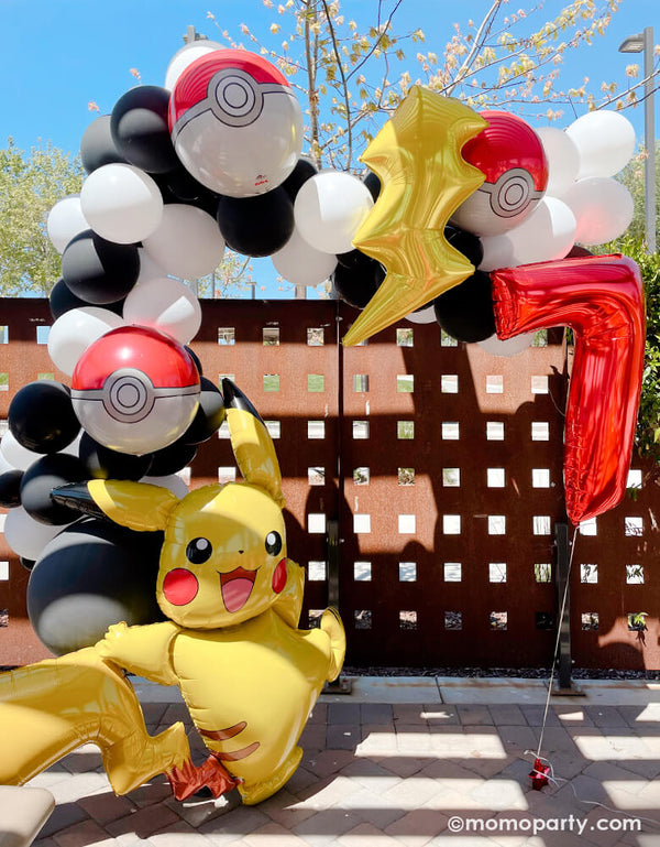 "Pokemon Party with a Black and white latex balloon garland, mix with Pokemon Pokeball Orbz Foil Balloon and Lightning Bolt Foil Balloon. A anagram 57"" Pokemon Pikachu Airwalker Foil Balloon stand on the left, and a Large Number 7 Red Foil Mylar Balloon on the right side. A modern cute backdrop for a 7 years' boy pokemon themed birthday party"