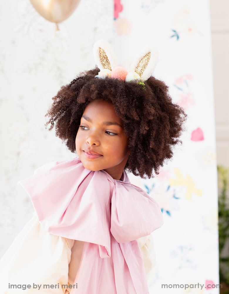 A little african american girl wearing a pink dress and a Meri Meri Pom Pom Bunny Ear headband with glittery ears and lots of colorful pompoms on her curly hair, for a cutest modern Easter celebration
