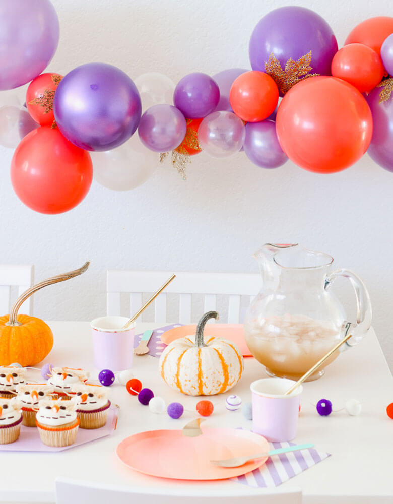 A kids fall party featuring Pumpkin plates with scarecrow cupcakes and a beautiful balloon garland of lilac, coral, and gold accents