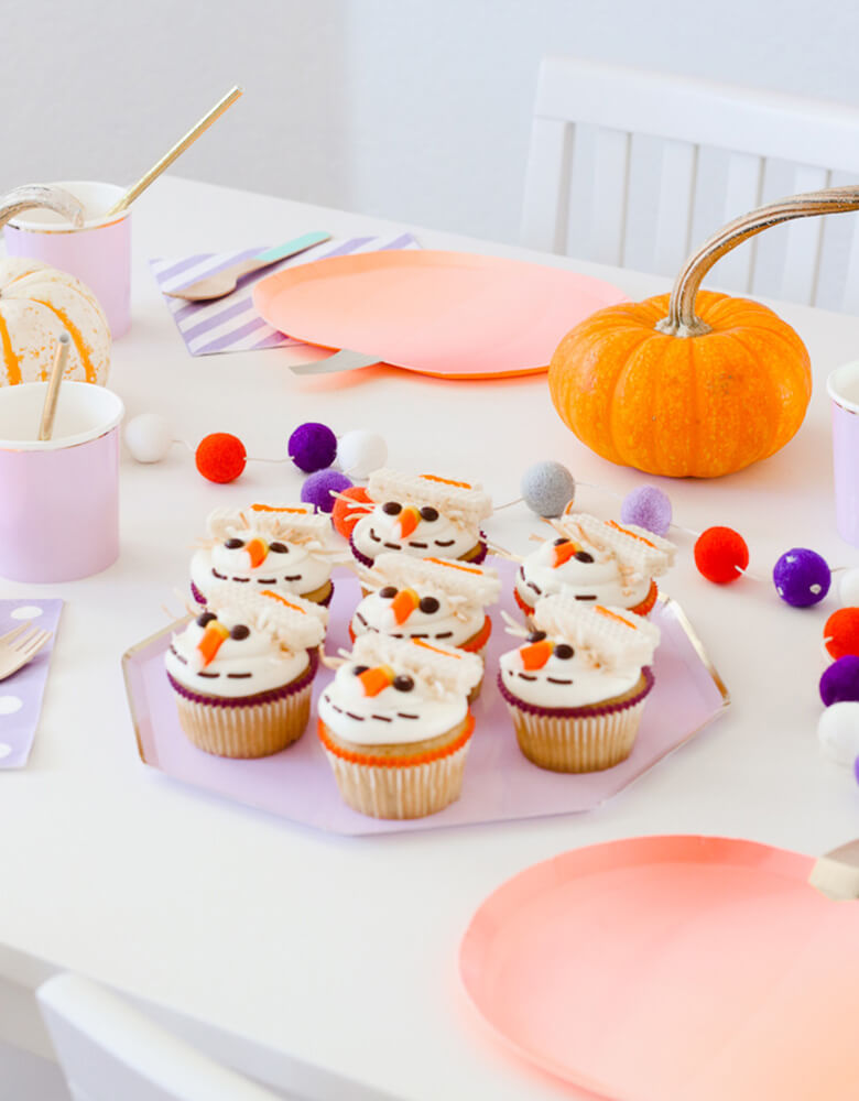 Pumpkin plates and lilac plates featuring scarecrow cupcakes for a Kids' Fall inspired party