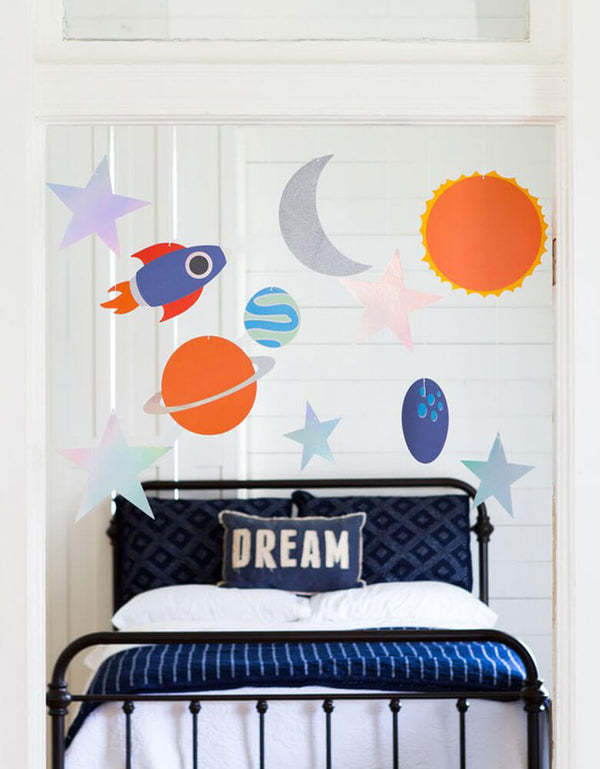 A space themed kid's room with My Mind's Eye Rocket Hanging Decors featuring rockets, planets, moon, sun