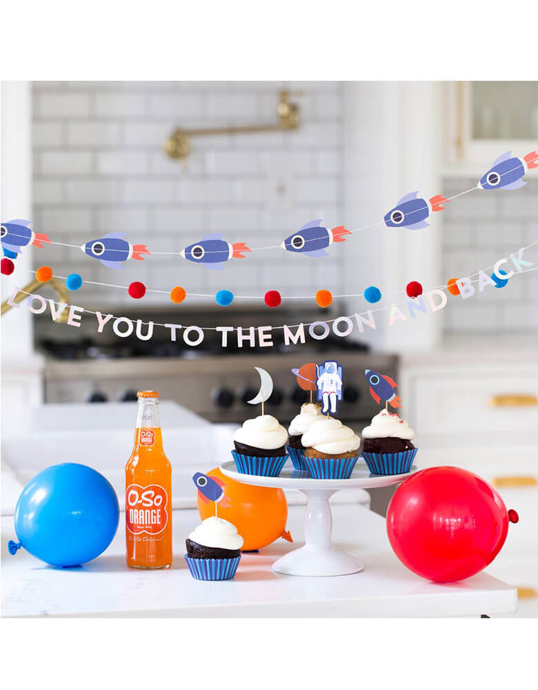 A space themed party table with My Mind's Eye Rocket Mini Banner Set hung above cupcakes and party balloons