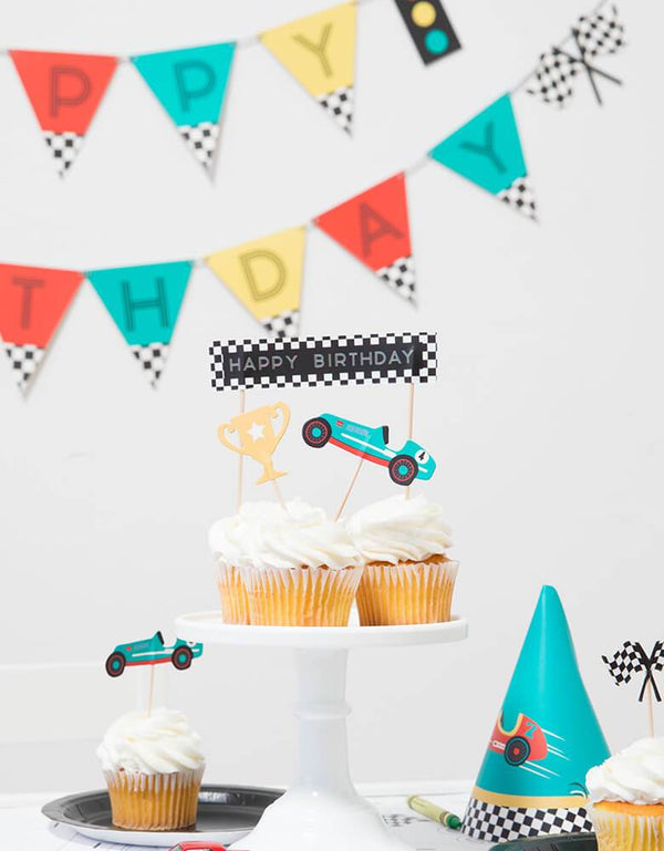 Merrilulu Race Car Toppers on cupcakes in a kid's race car themed party with colorful garland hung and birthday hats