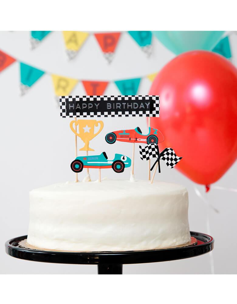 Merrilulu's Race Car Toppers on a birthday cake in a kid's race car themed party with colorful garland and balloons hung on the wall