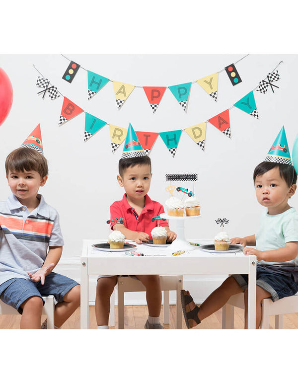 A Race car themed birthday party with three boys featuring Merrilulu Race Car Happy Birthday Banner Set on the wall with color flags and checkered race car flag designs. On the party table there's cupcakes topped with merrilulu's race car cake toppers