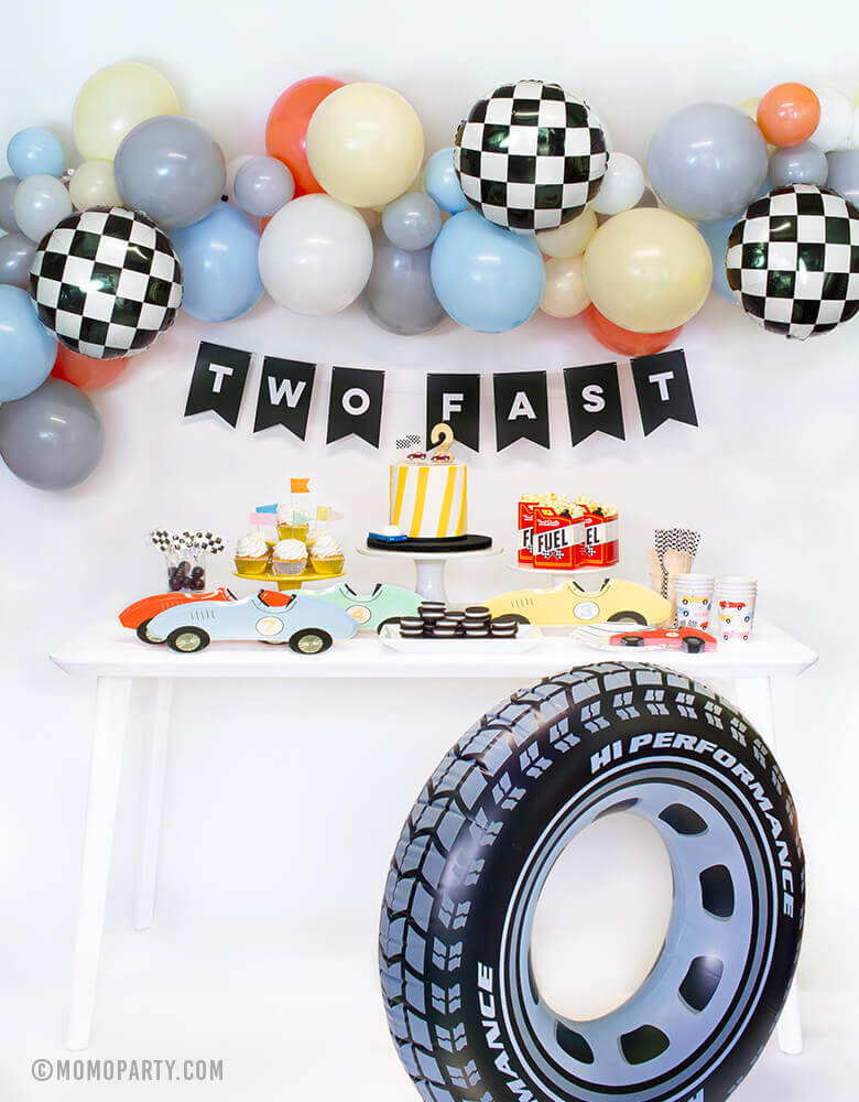 "Momo Party Race Car Box, set up inspiration with Meri Meri race car paper plates, race car shape napkins, race car graphic party paper cups, black strip small plate, neon confetti flag cupcake kit, race Car candles and gold #2 candle over a cake, Fuel treat favor box with popcorns as tableware, colorful balloon cloud, black costume letter banner with script of ""Two Fast"", checkerboard foil balloon and Inflatable giant tire tube as decorations,  for a 2 years old modern Race car, car themed birthday party"