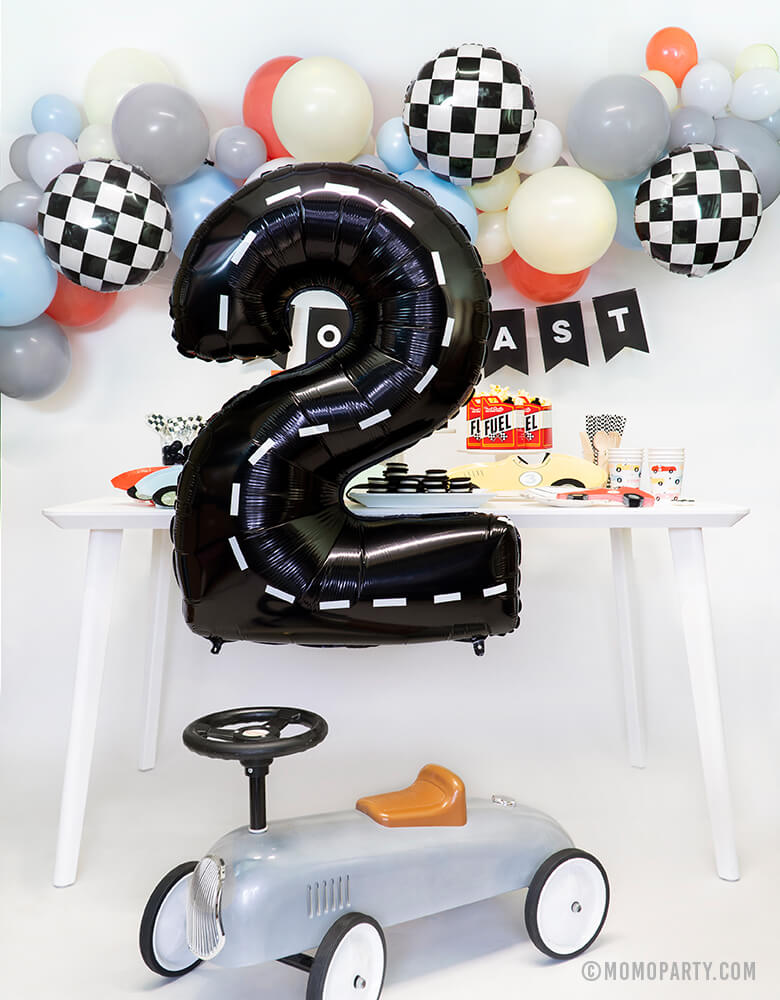 Modern Race Car party set up idea with Large Black number 2 foil balloon with decoration strip for a 2 years old Race Car themed birthday party