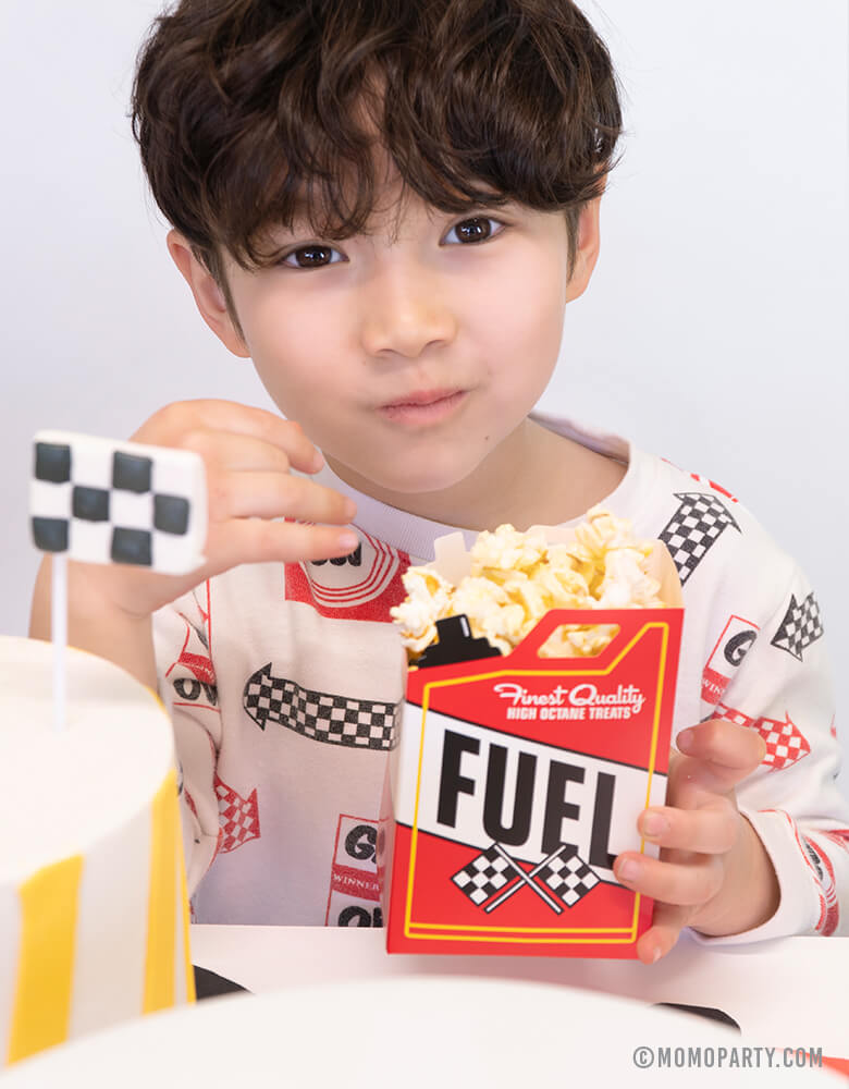 boy eating popcorns with a Fuel-Treat-Favor-Boxe at a Car themed birthday party