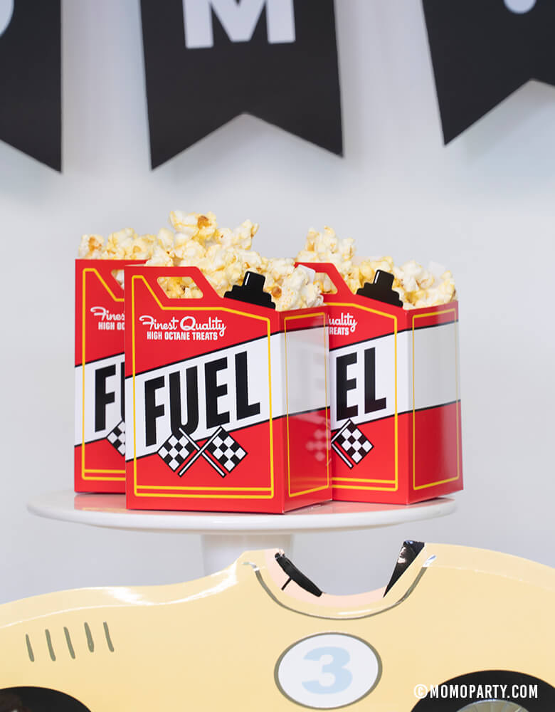 3 Fuel-Treat-Favor-Boxes with full of popcorn on top of cake stand at a Car themed birthday party