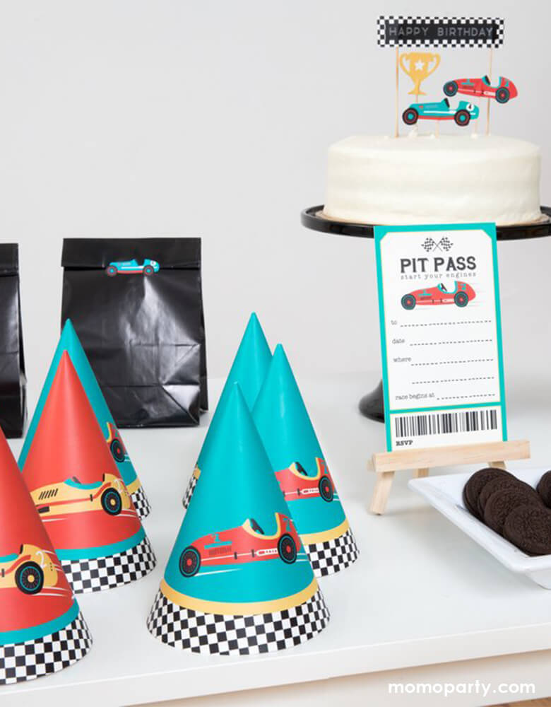 Race car birthday party, dessert table decorated with a white cream cake with race car cake toppers, a PIT PASS card,cookies, Race car party hats, gift bags