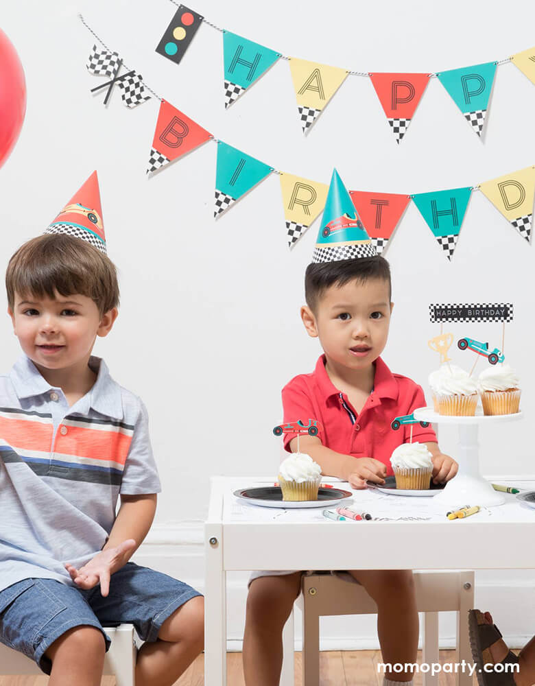 Boys wearing Race Car Party Hats and eating cupcakes at a Vintage race car birthday party
