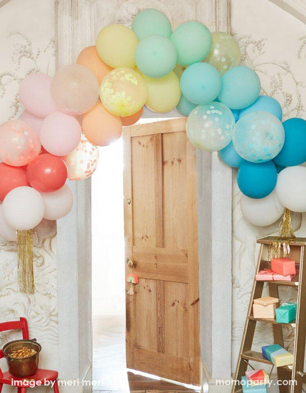 A room decorated with Meri Meri's Rainbow Balloon garland Arch Kit with multicolored balloons, confetti balloons, and gold tinsel  hung over the door of the room